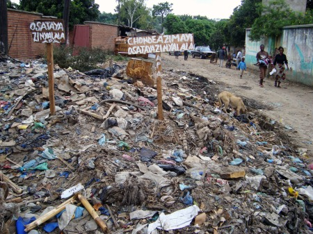"""A """"do not litter"""" sign surrounded by a sea of garbage in Malawian suburb, Ndirande. The roadside has become an informal dumpsite for residents and market traders. Photo by Sarah Berman."""